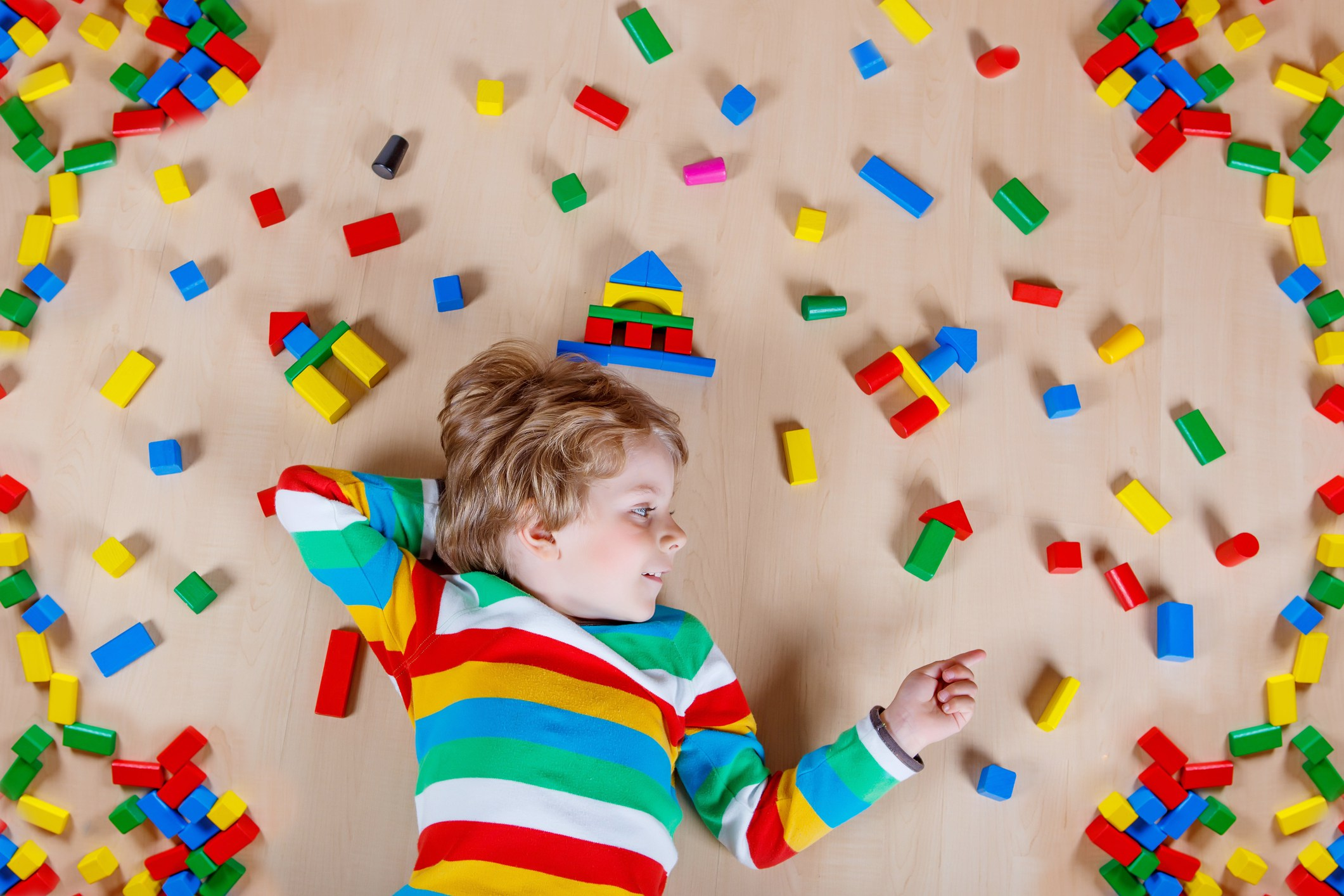 Little blond child playing with lots of colorful wooden blocks indoor. Active kid boy wearing colorful shirt and having fun with building and creating.